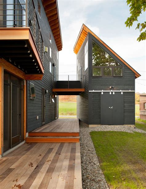black house with angled roof balcony barn doors breezeway