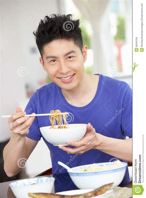 brustmuskeltraining zu hause mann junger chinesischer mann der zu hause sitzt mahlzeit