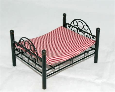 bed check black framed bed with red checked mattress