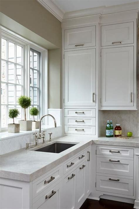crisp white shaker cabinets go to the ceiling in this