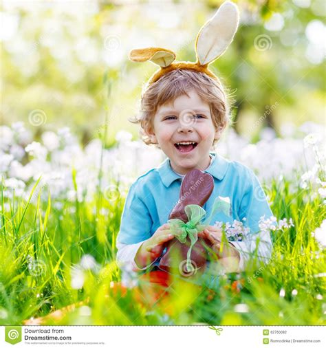 5 Adorable Families Celebrating Easter by Kid Boy Chocolate Easter Bunny Stock Photo