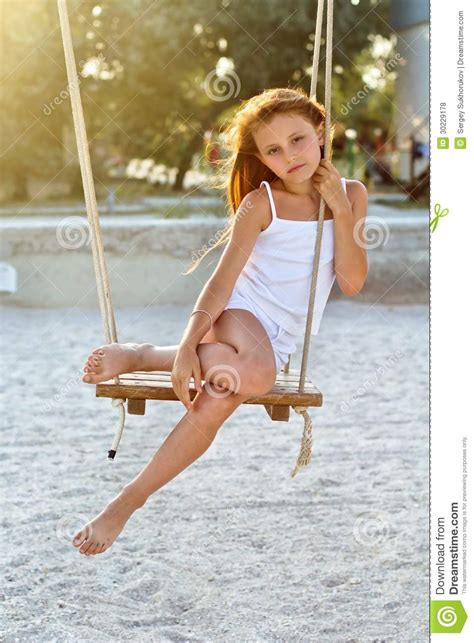 sitting swing little girl sitting on a swing royalty free stock photos