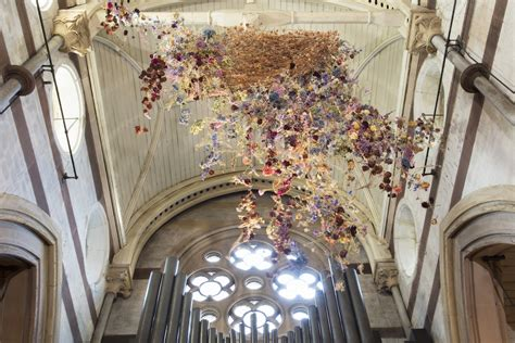 installation art features thousands  flowers suspended