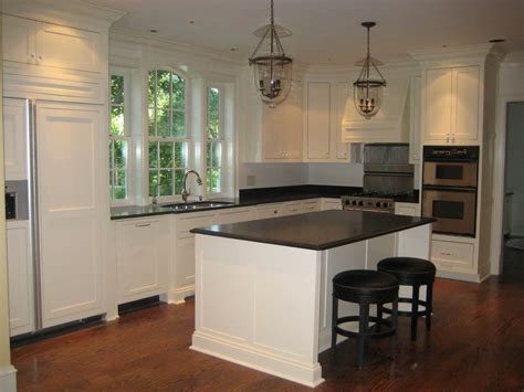 white kitchen island with black granite top white cabinets with chunky crown moulding and window