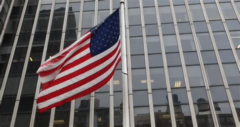 american flag flying front of steel and glass corporate