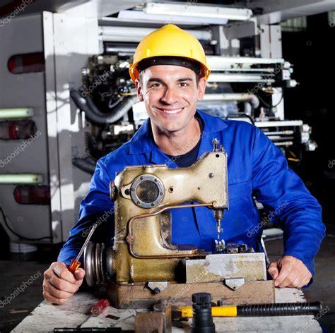 mechanic repairing industrial sewing machine stock photo