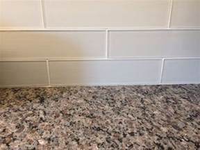 new caledonia granite countertops and white glass tile