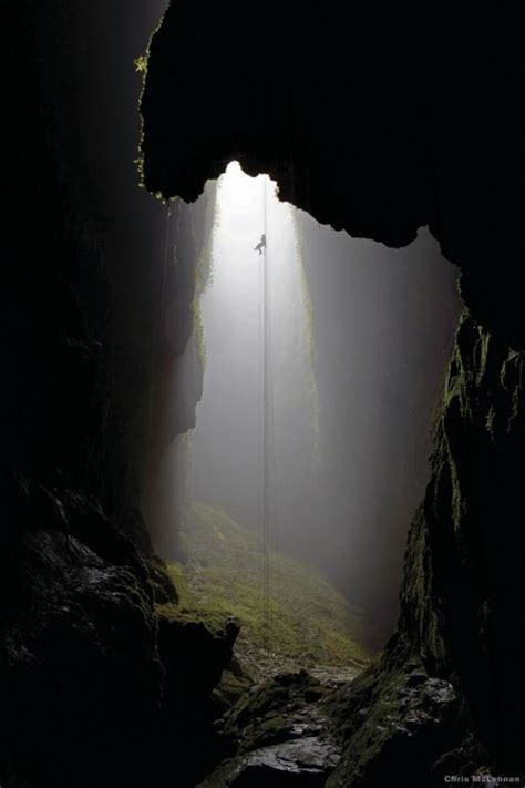caving helmet with light into a moss grown cave its a climb out caving
