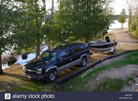 fishing boat with motor a pickup truck with a trailer and fishing boat with motor
