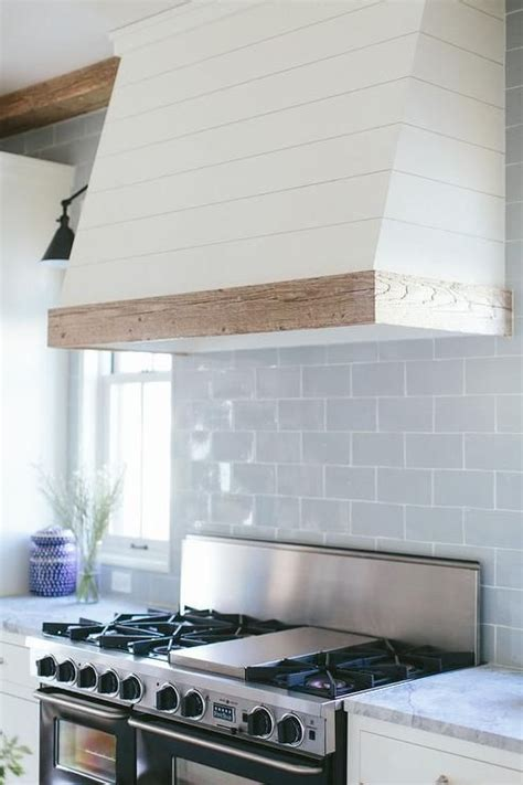 white symmetrical kitchen range with natural wooden love the white natural wood trim also the tile blue