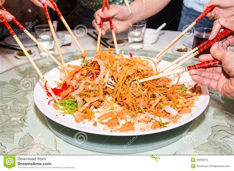 new year mixing dish a of mixing and tossing yee sang dish with