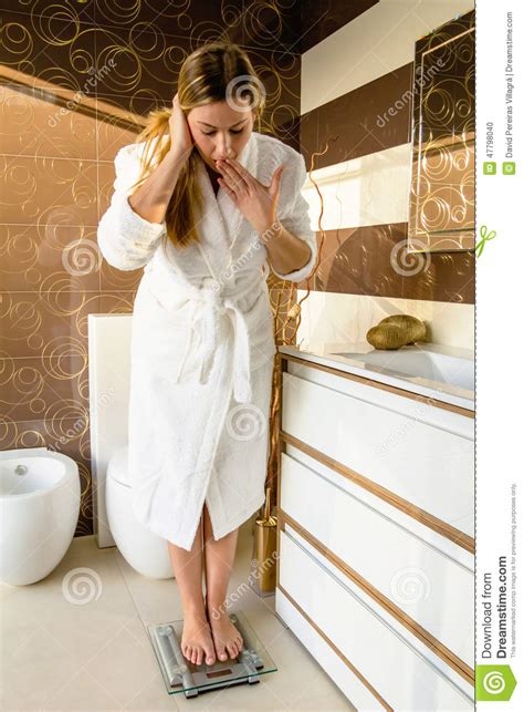 stand up bathroom scales woman standing on bathroom scale frustrated with stock