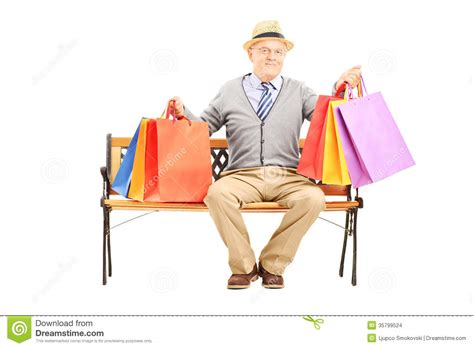 bench shopping smiling senior man seated on a wooden bench holding