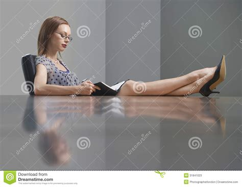 Comfortable Chair For Reading businesswoman reading book with feet on conference table