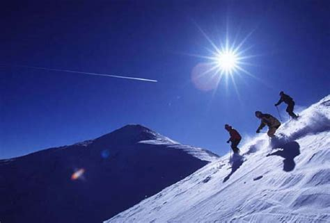 Compared To Yellow Light Orange Light Has by Photos Of Skiers On White Slope With Blue Sky And