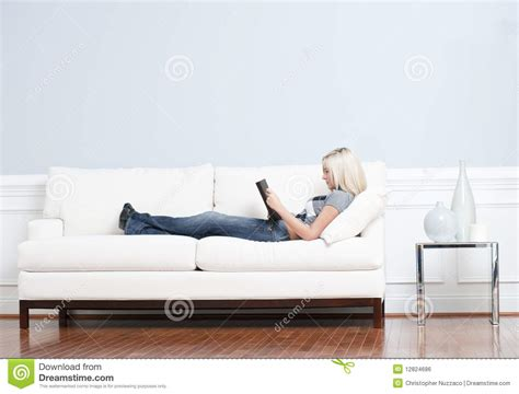 woman reclining woman reclining on couch with book royalty free stock