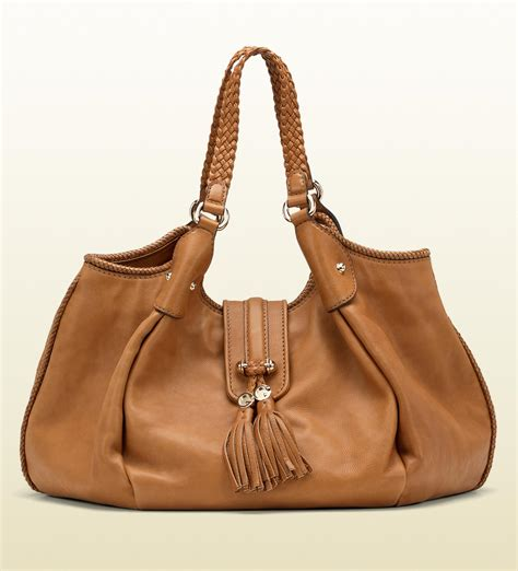 gucci marrakech medium shoulder bag with woven leather trim and tassels with metal g details in