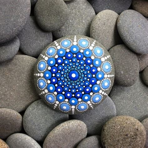 artist creates colorful mandalas by painting ocean stones