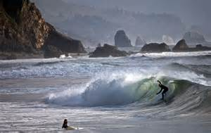 a surfer catches a wave at indian beach in ecola state park