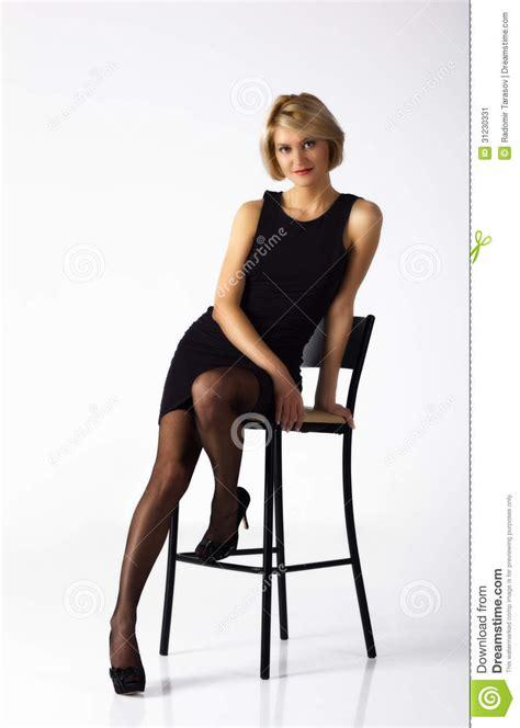 seduta sulla faccia donna in vestito nero che posa seduta su una sedia