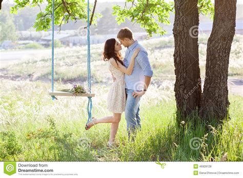 swing couple young kissing couple under big tree with swing stock photo