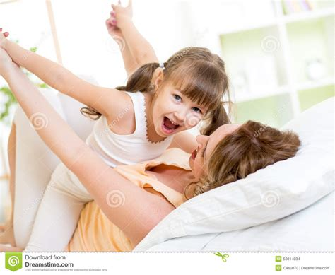 fun in bed mother and child having fun in bed stock photo image