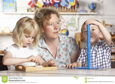 pre image helping two children at montessori pre royalty
