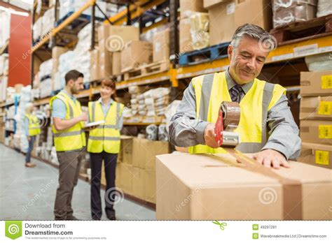 warehouse worker sealing cardboard boxes for shipping