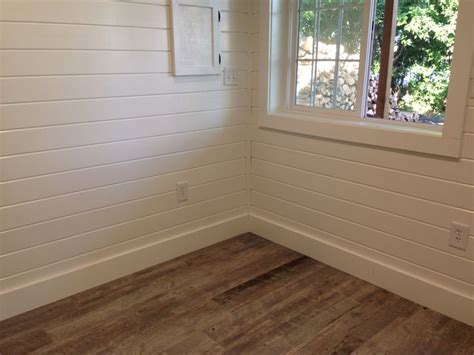 ceramic tile plank floors painted white pine tongue and groove walls in the changing room of
