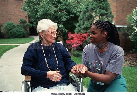 Retirement Home Volunteer In Wheelchair Stock Photos In