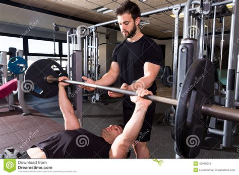 how to bench press a person bench press weightlifting man with personal trainer stock