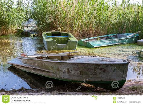 length of a rowboat one rowboat half a length out of the water on the shore
