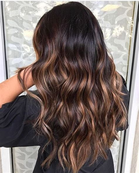 Picture Of wavy black hair with caramel highlights looks