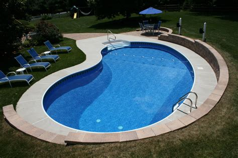 kidney pool a kidney shaped pool with brushed concrete decking and a