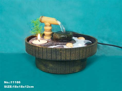 zen garden water fountain with sand rocks and tea candle