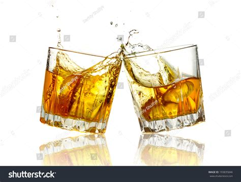 glasses clinking two whiskey glasses clinking together isolated stock photo