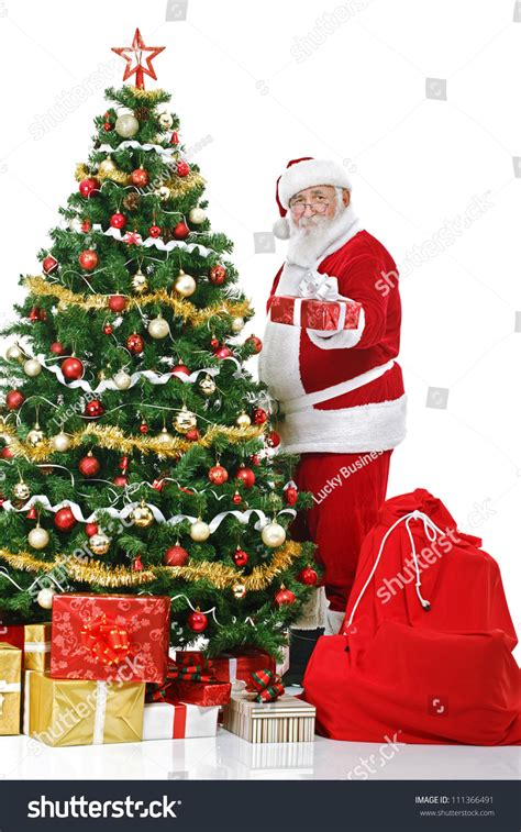 img of santa claus and x mas tree santa claus standing next decorated tree and holding gift and isolated on white