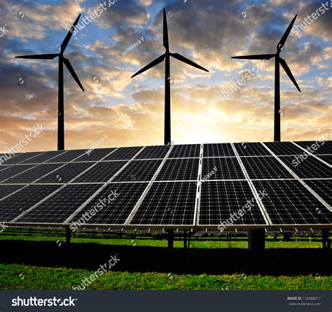 solar energy panels with wind turbines in the sunset stock