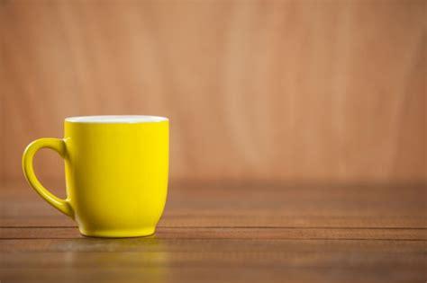 yellow coffee mug on wooden table photo free