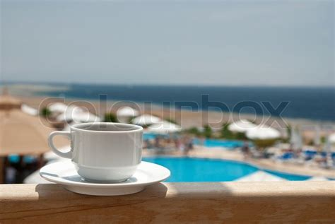 coffee shop near white house white cup of coffee near sea beach and pools stock photo