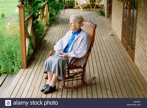 in home sitting sitting in rocking chair on veranda at home stock photo royalty free image