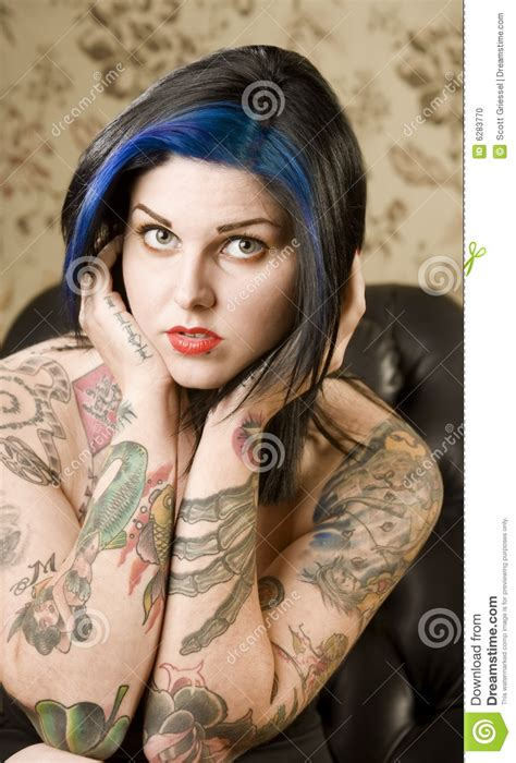pretty woman with tattoos in a leather chair stock photo