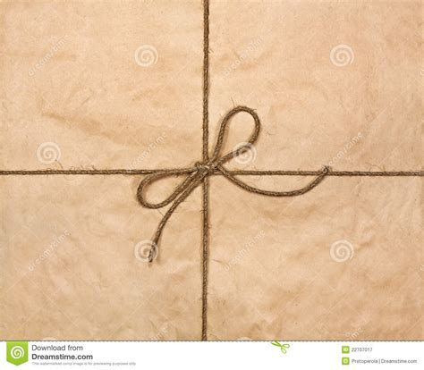 String On Paper - string in a bow on a brown recycled paper royalty