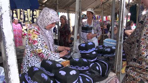uzbek women selling traditional wedding skullcaps and dresses sunday margilon uzbekistan 10 june 2013 veiled women discuss