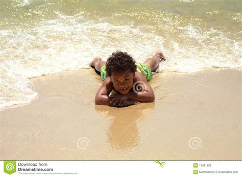 Surf The Web Laying by Boy Laying On Sand Stock Photography Image 19481692