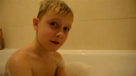 1 girl 1 bathtub the child bathes in a bathroom with water foam blond boy
