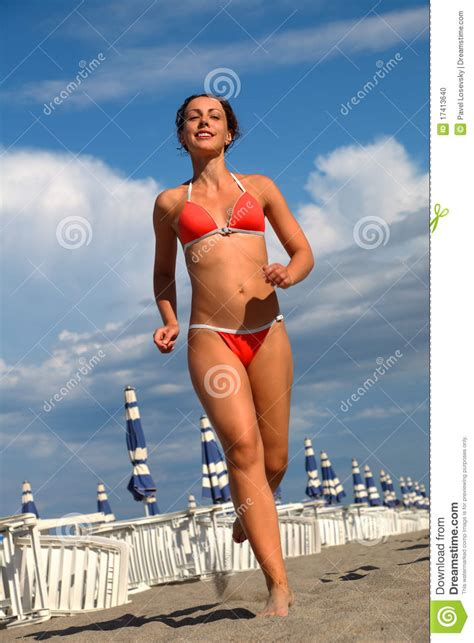in bathing suit runs on sand on stock photo