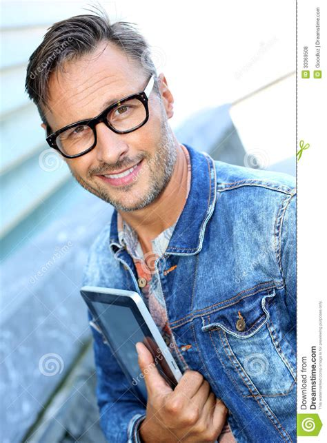 middle age trendy clothing trendy middle aged man with tablet in hand stock photo