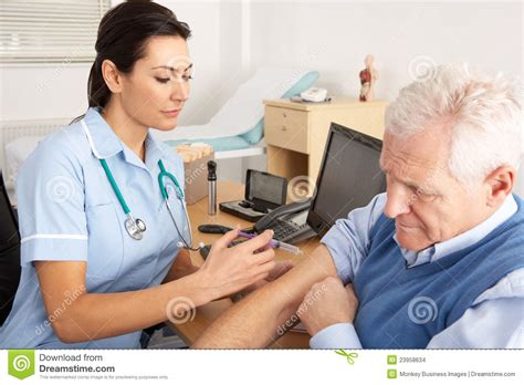 giving injection to senior stock images