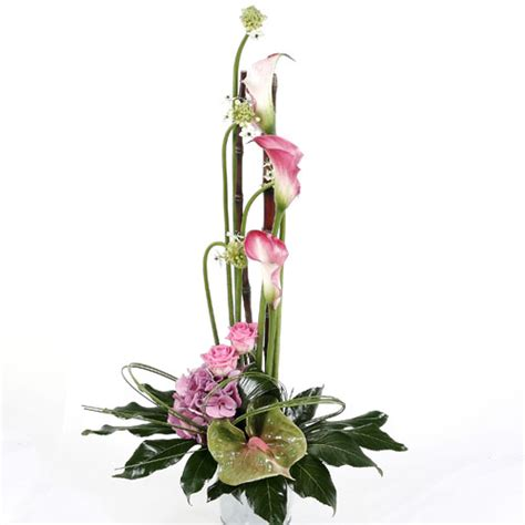 tall arrangement using pink tropical flowers and exotic foliages